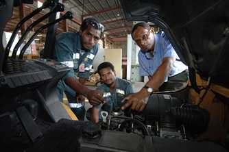 Young men learn about mechanics at the Australia-Pacific Technical College, in Fiji. Photo by Rocky Roe for AusAID