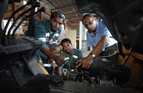 An instructor assists two young men to examine an engine.