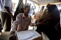 A woman has her ration card checked at the Ifo refugee camp in Dadaab, Kenya.