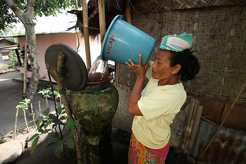 In Lombok, Indonesia, a woman pours clean water from the central source into her covered storage container. Photo by Josh Estey for AusAID