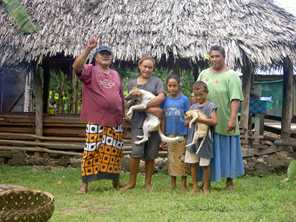 A Samoan family stands outside their traditional open-walled house. Photo by Plenz/Wikimedia