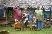A Samoan family stands outside their traditional open-walled house.