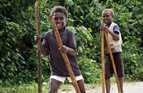 Boys walking on stilts in Solomon Islands.