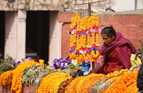 A woman sells strings of colorful flowers.
