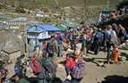 Locals and tourists buy items at a market on a narrow ridge of a village in a in mountainous area.