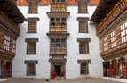 The Trashigang Dzong or Buddhist monastery in eastern Bhutan has distinctive white towering walls surrounding its courtyard.