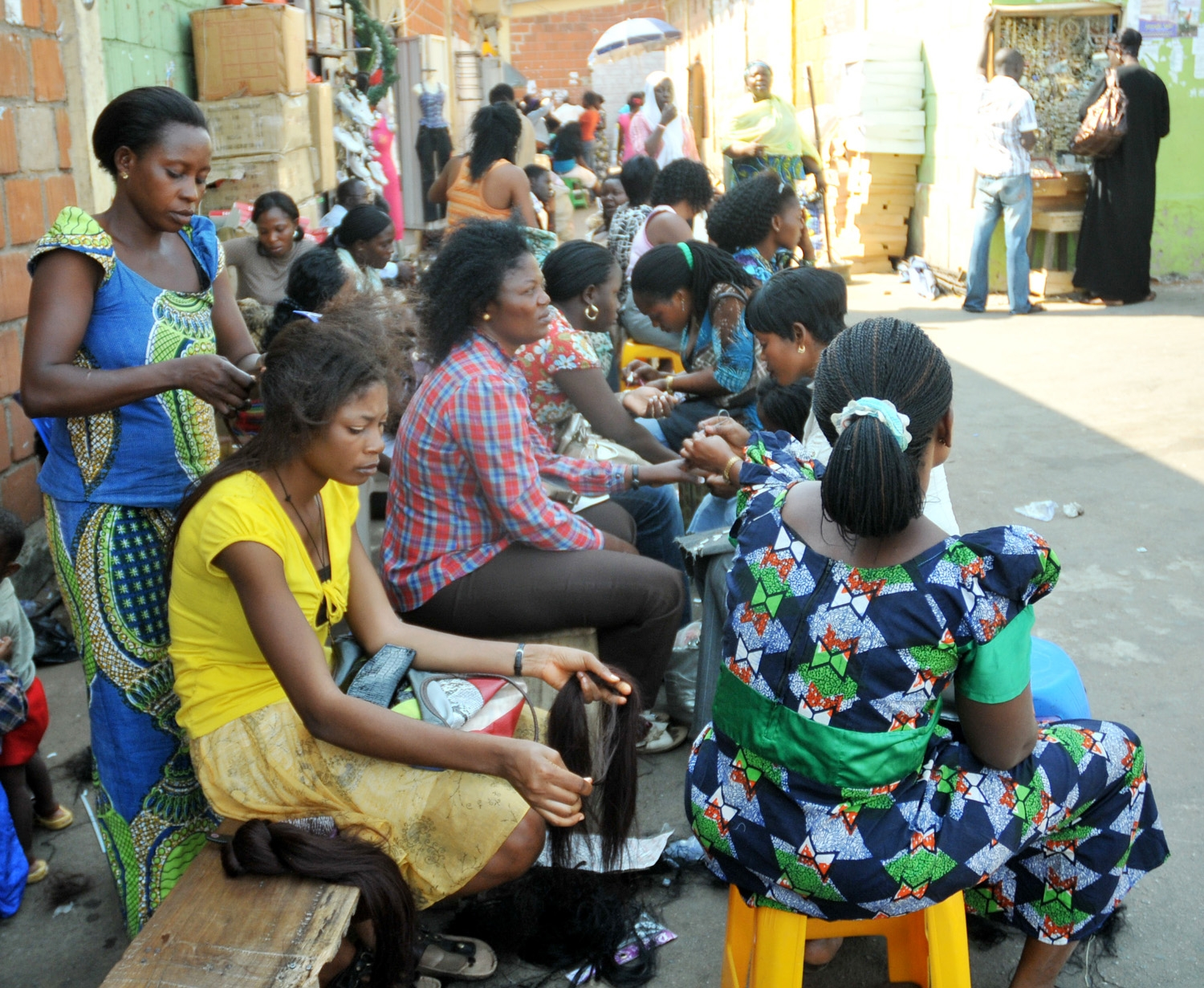 Women have their hair braided at Wuse market in Abuja, capital of Nigeria, for Christmas festivities. Photo © li huailin/Xinhua Press/Corbis