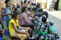 Women have their hair braided at Wuse market in Abuja, capital of Nigeria, for Christmas festivities.