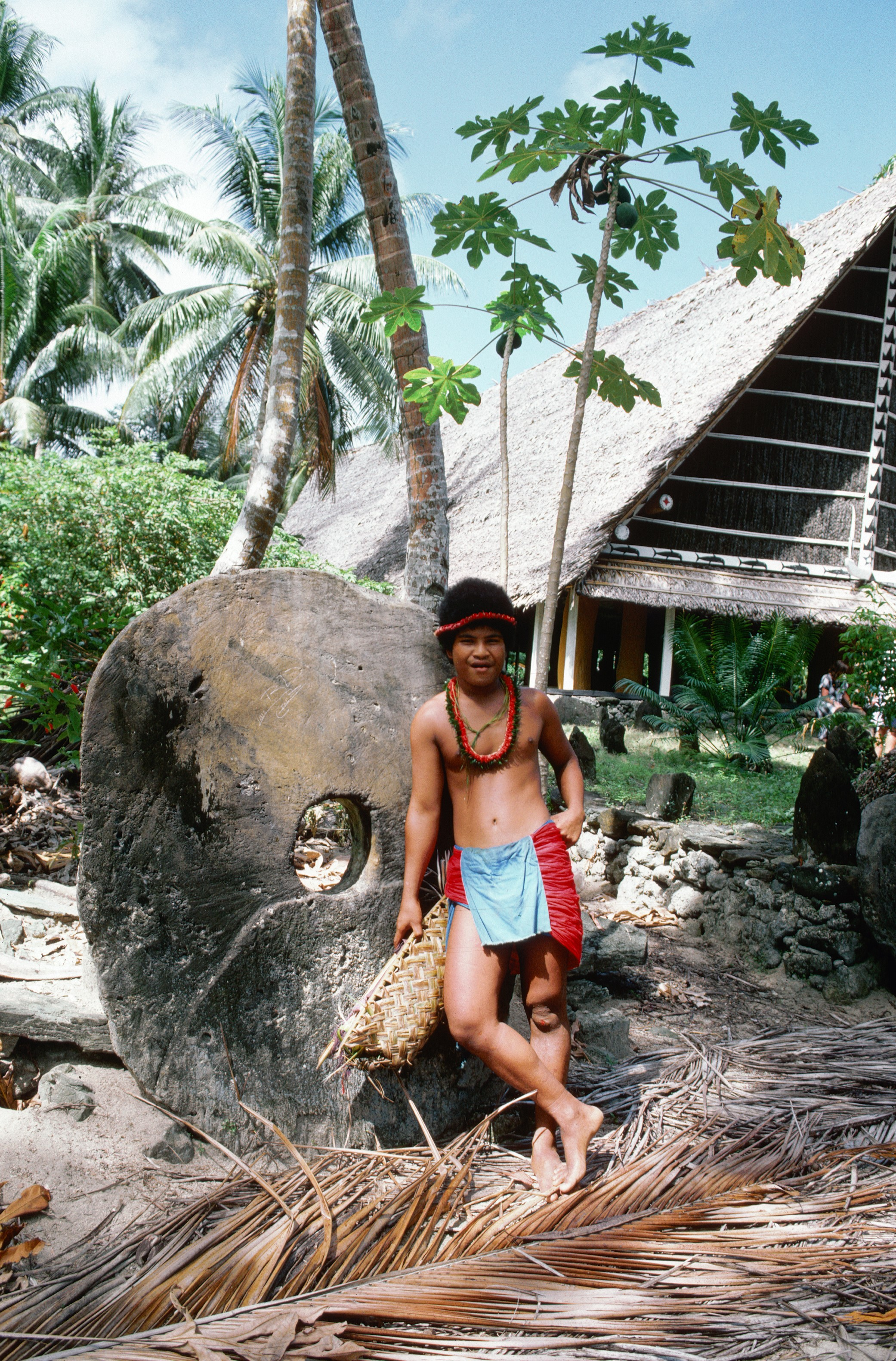An islander boy leans against traditional stone money in front of a traditional community house on Micronesia's Maap Island. Photo © Wolfgang Kaehler/CORBIS