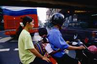 A family riding a motorcycle in Bangkok, Thailand