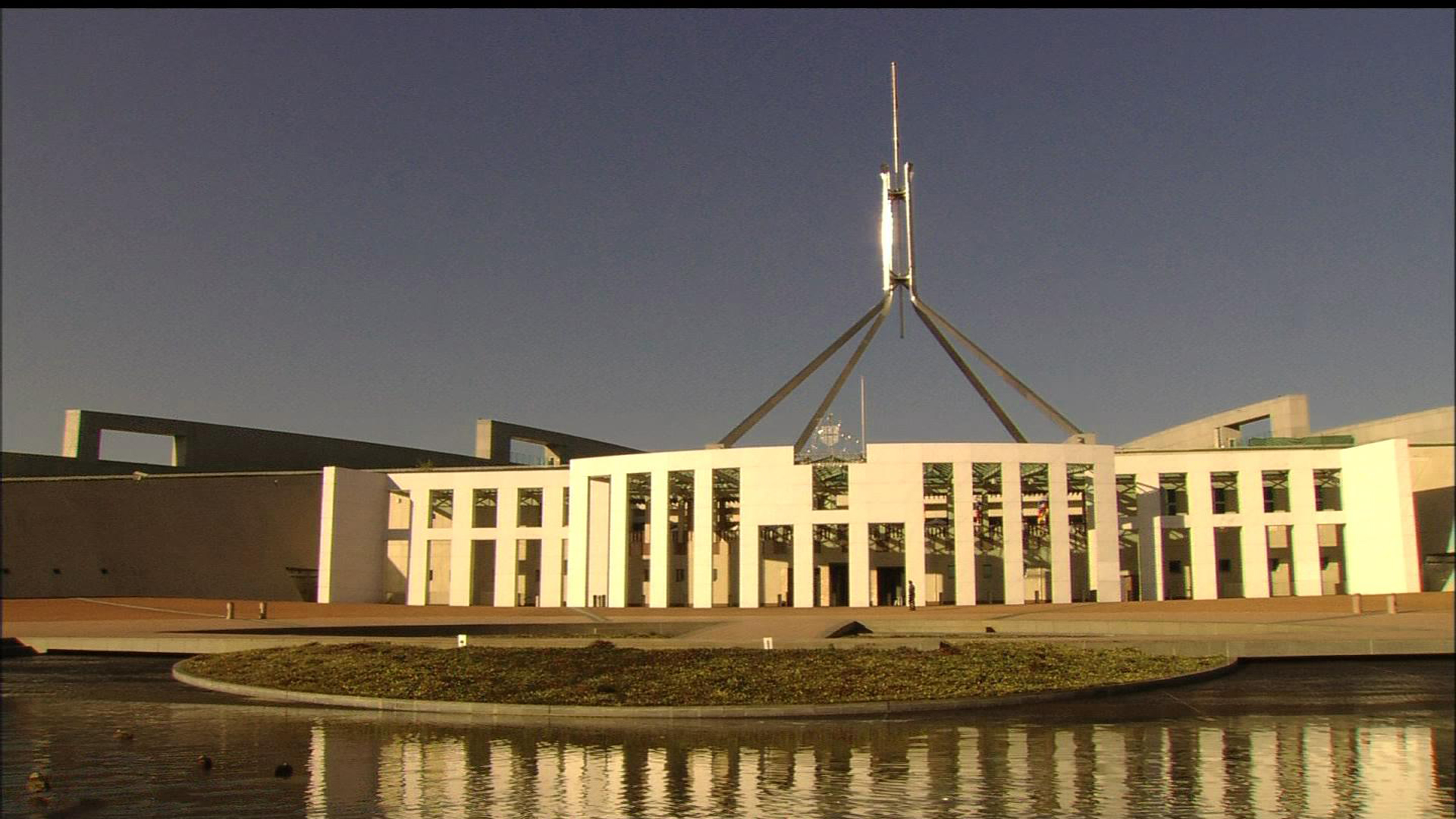 With its giant flag mast, Parliament House, home of the federal government, dominates Capitol Hill, Canberra, Australia. This image is from Wikimedia, and is in the public domain.