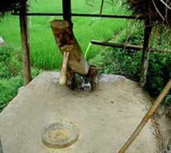 A stream of water drives a heavy wooden beam up and down to pound rice into flour in this simple rice mill. B. Baldock