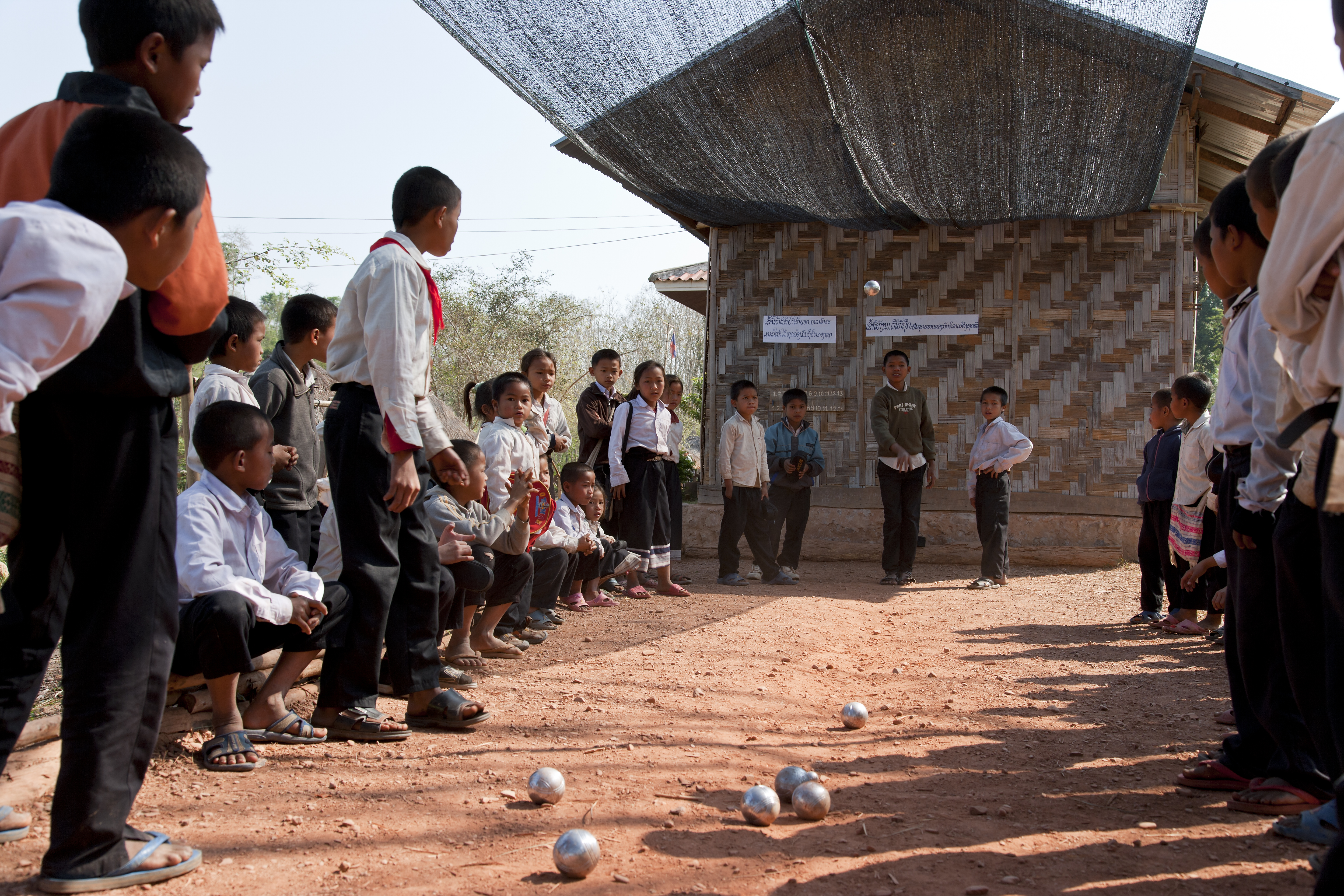 Boys are playing petanque at a mountainous village school in Laos. Photo by Bart Verweij for AusAID