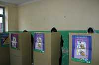Three women hidden behind election booths cast their secret vote.