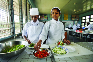 Two female students prepare a salad in a kitchen at the Australia-Pacific Technical College in Fiji.