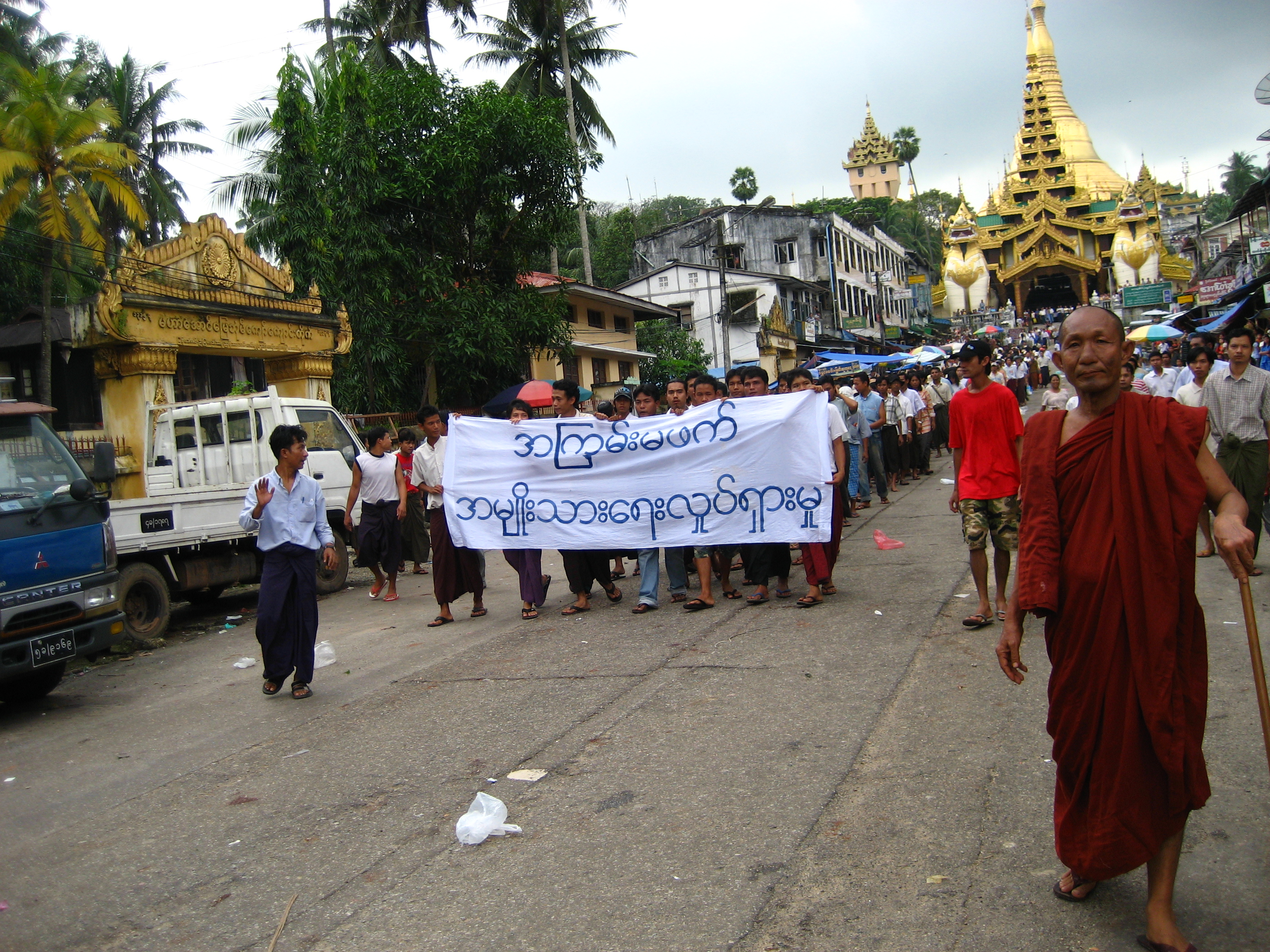 Protesters with a banner that reads 'Non-violence: national movement' parade past Shwedagon pagoda in Yangon, Myanmar. Photo by Racoles/Wikimedia CC BY-NC-ND 2.0 licence