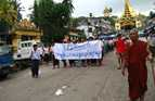 Protesters with a banner that reads 'Non-violence: national movement' parade past Shwedagon pagoda in Yangon, Myanmar.