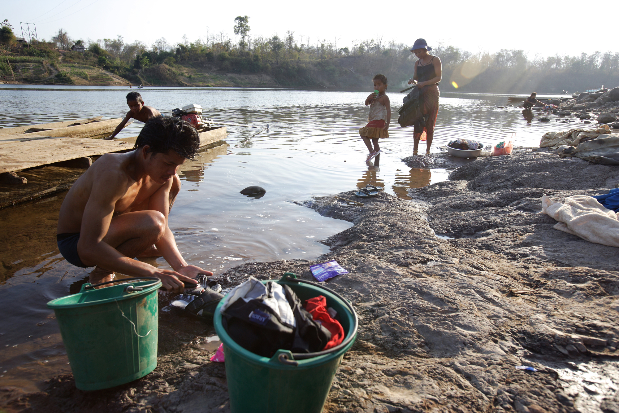 People bathe and do their laundry on the banks of the Sekong River in southern Laos before it joins the Mekong River. Photo by Jim Holmes for AusAID