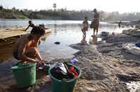 People bathe and do their laundry on the banks of the Sekong River in southern Laos before it joins the Mekong River.