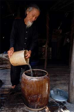 Quach Thoi Dai pours dirty water into a large container lined with alum to make sediment fall to the bottom. Photo by Will Salter for AusAID