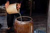 Quach Thoi Dai pours dirty water into a large container lined with alum to make sediment fall to the bottom.
