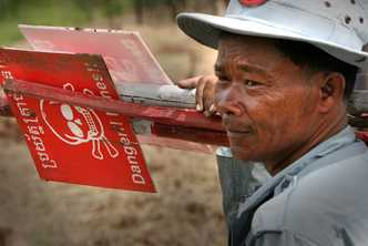 Signs warn people of landmines and other dangerous items in Cambodia. Photo by Kevin Evans for AusAID