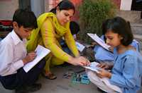 A teacher helps her students in Pakistan.