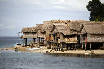 Houses with woven bamboo walls and thatched roofs, built along the coast in Solomon Islands, are vulnerable to storm surges. Photo by Rob Maccoll for AusAID