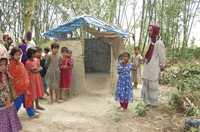 Mosmoil villagers stand outside a sanitary latrine.