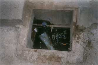 Before new taps were installed, dirty water filled the pit of this public tap in Cement Huts, Bangalore, India, contaminating the water supply. Photo by AusAID