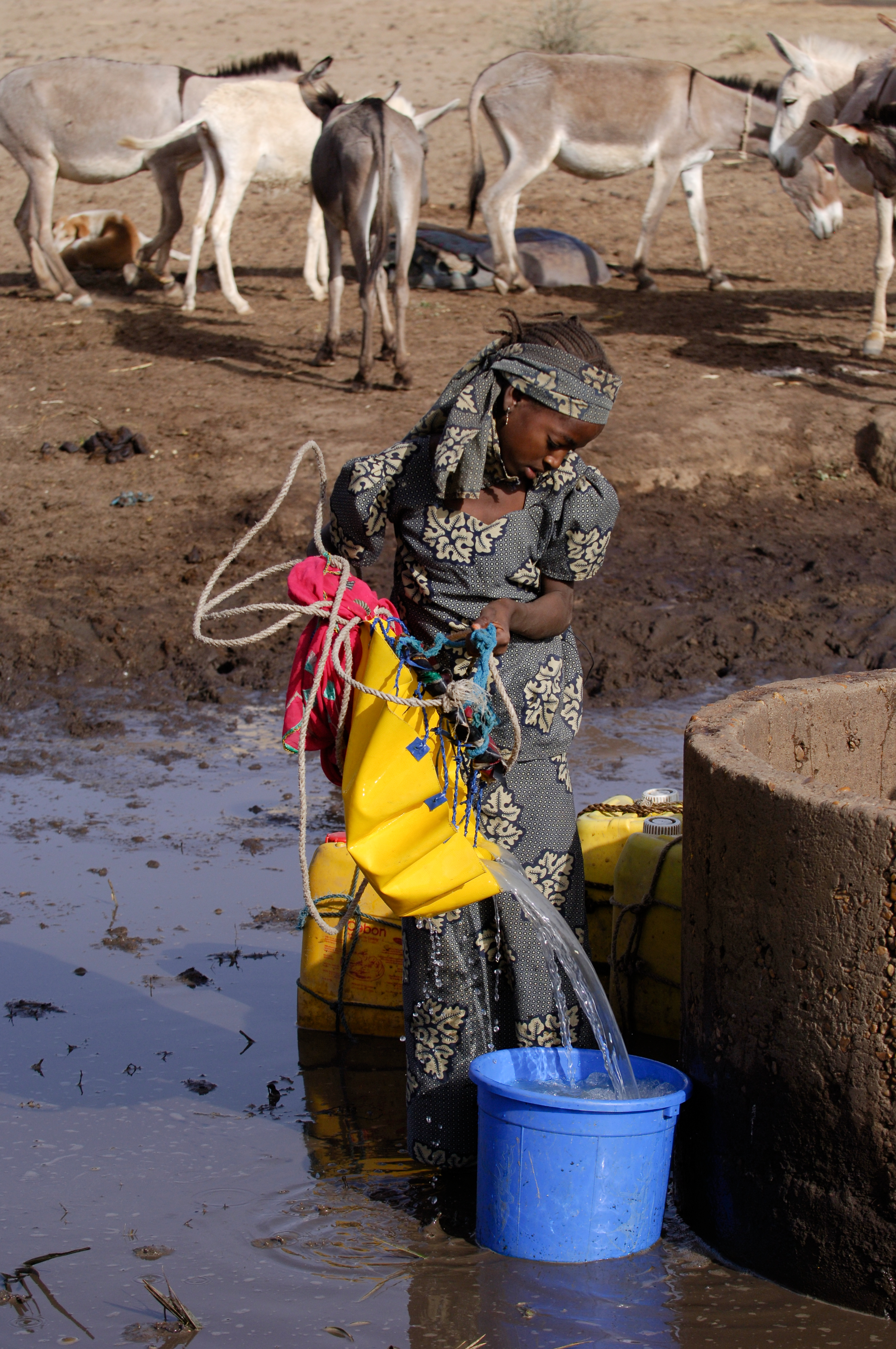 In Niger, Zelifa hauls water from a well using a flexible bucket. Photo from World Vision Australia