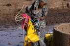 In Niger, Zelifa hauls water from a well using a flexible bucket.