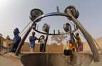 In Niger, this well and its surrounds have been sealed with concrete, and wheel hubs are mounted to act as pulleys.