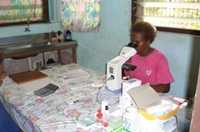 A microscopist analyses a blood sample for active plasmodium, in Solomon Islands.