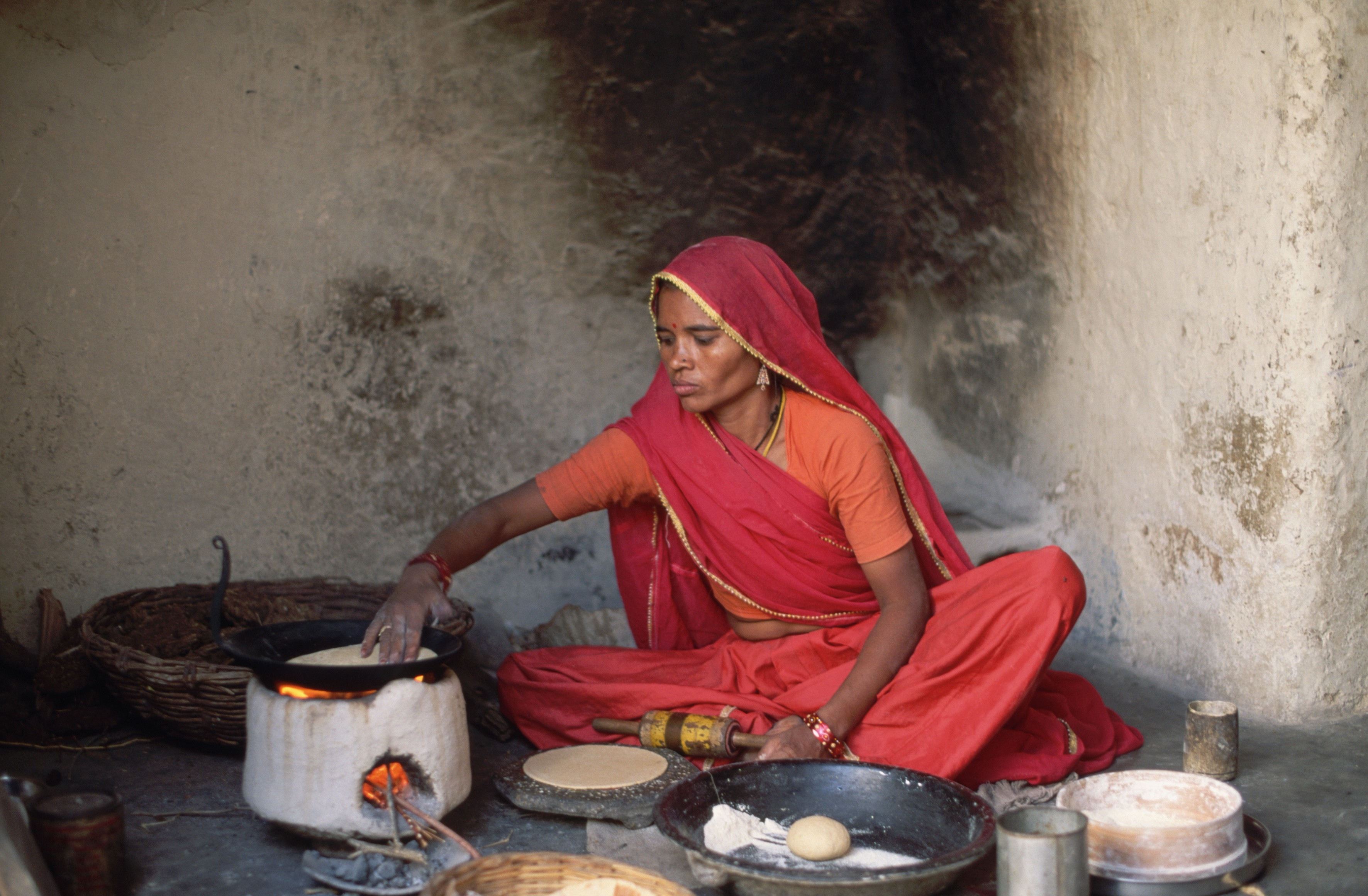 A woman bakes flat bread on a fuel efficient stove in Tilonia in north-east India. Photo © Albrecht G. Schaefer/CORBIS