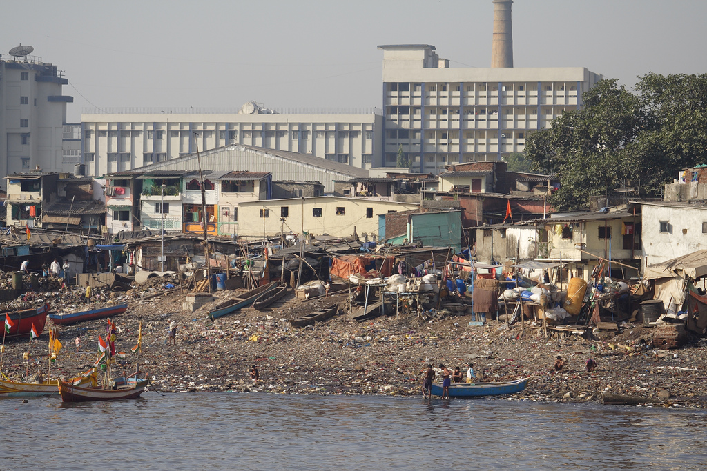 Slum housing is built along the polluted river, while modern housing is further away in Mumbai, India. Photo by Dirk Guinan for AusAID