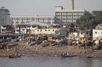 Slum housing is built along the polluted river, while modern housing is further away in Mumbai, India.