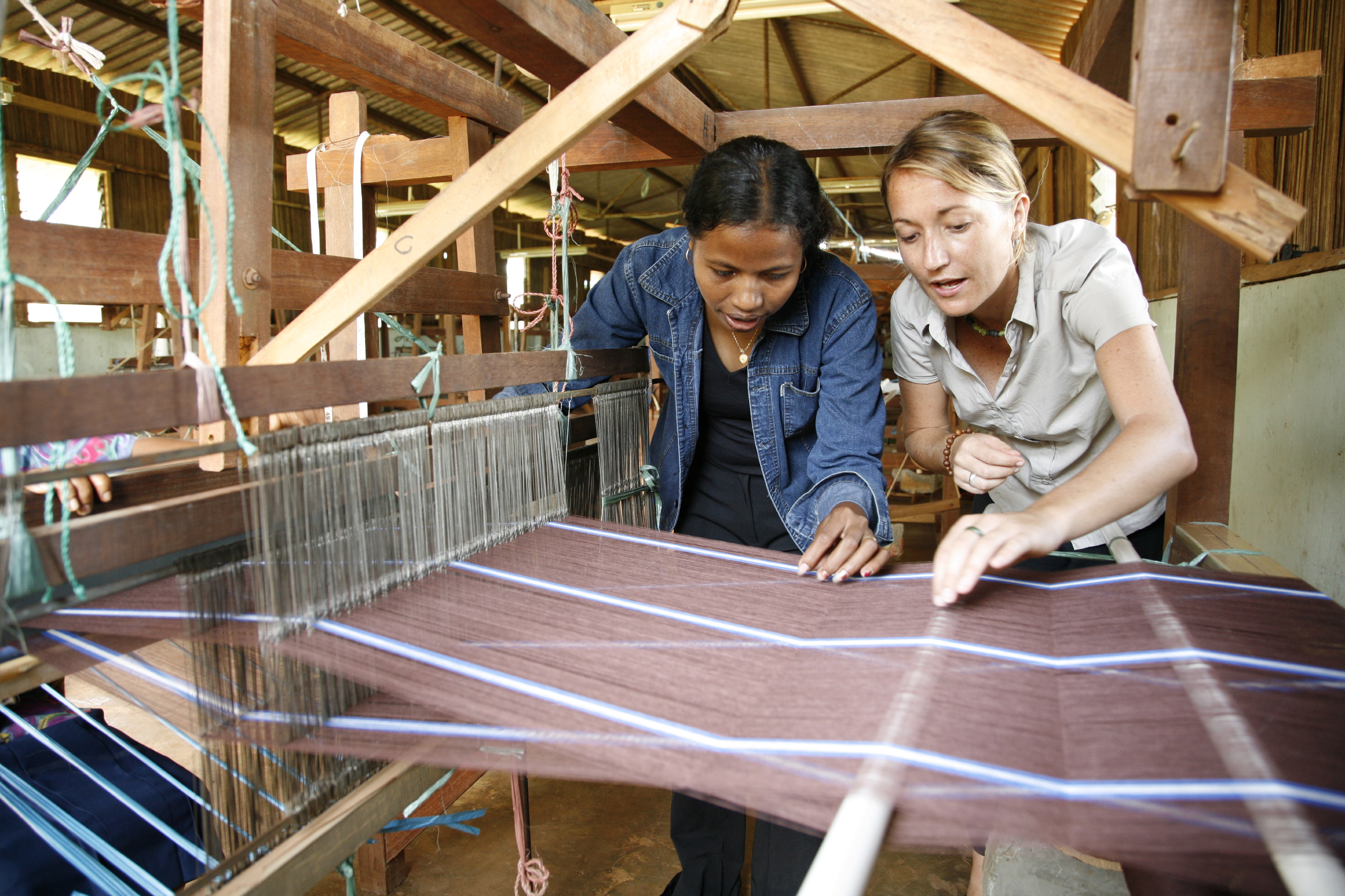 Australian volunteer Louise Higgins helps a local woman set up a floor loom ready for weaving. Photo by Debra Plueckhahn/Australian Volunteers International