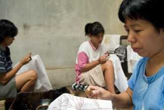 Batik-makers put wax on cotton at a batik workshop in Indonesia. Photo by Ahmad Salman for AusAID