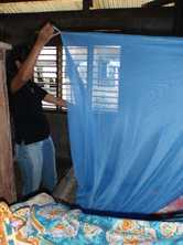 A woman installs a bednet above her bed to reduce the chance of being infected with malaria in the Philippines. Photo by Rowena Harbridge for DFAT
