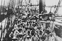 Pacific Islanders from Solomon Islands and Vanuatu standing on the deck of a sailing ship.