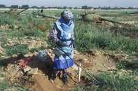 A de-miner with protective clothing uses a metal detector to search for landmines in farming ground.