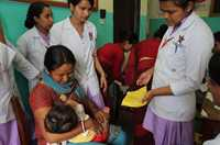 Medical personnel provide care to a mother and child.
