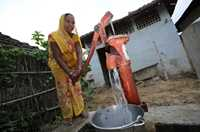 A woman pumps water into a bucket outside her home.