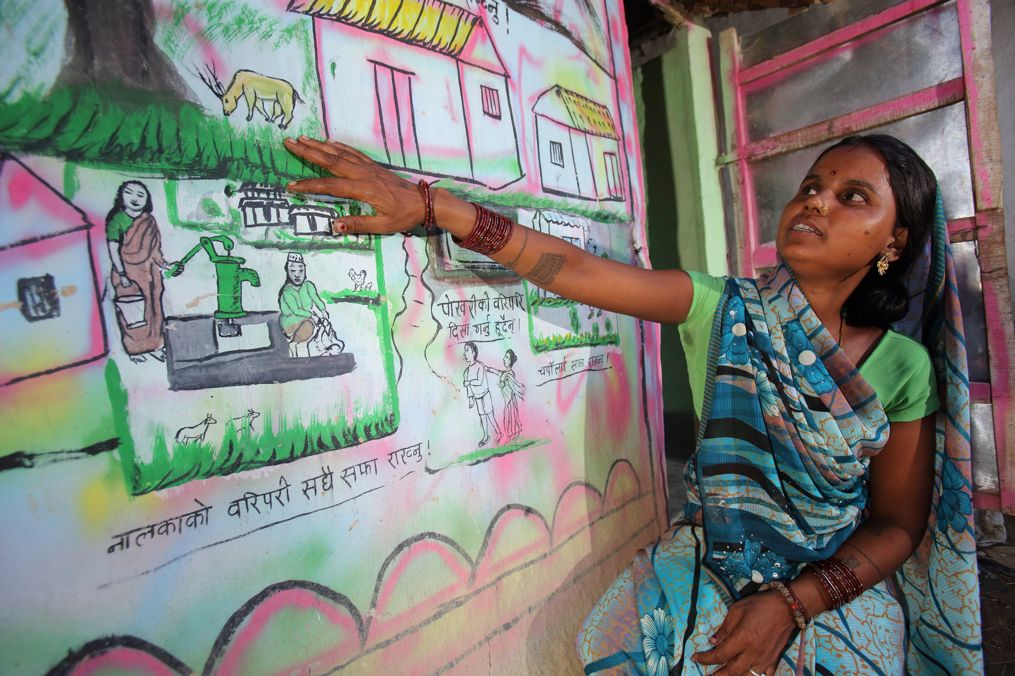 Aasu Ram explains her toilet mural highlighting the spread of disease in open defecation, Bastipur, Nepal Photo by Jim Holmes for DFAT