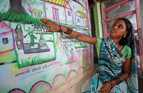 A woman points to hand-drawn pictures on a wall showing the impact of open defecation.