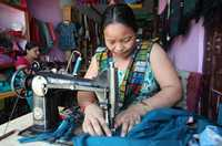 Two women use sewing machines to make clothes.