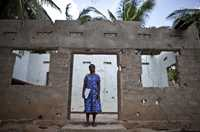 A Tamil woman stands inside the shell of her bombed out home in northern Sri Lanka.