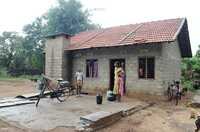 A woman stands outside her newly built concrete block home. It has a tiled roof.