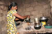 A woman prepares a meal in the kitchen of her concrete block house.